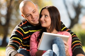 Male And Female Look At Electronic Tablet In Park