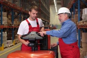 A senior worker teaching his junior the operation of a fork lift vehicle in a factory